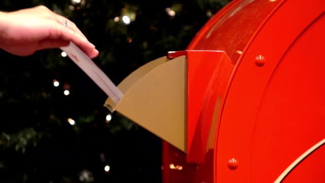 vídeos de stock e filmes b-roll de person putting letter into mailbox for santa claus in slow motion - correio