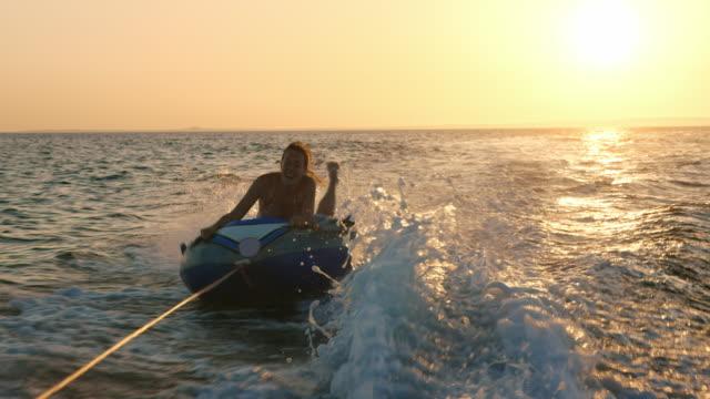 stockvideo's en b-roll-footage met slo mo persoon rijden op een opblaasbare buis bij zonsondergang - opblaasband