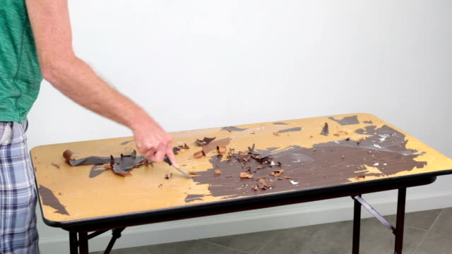 Person Scraping a Particle Board and metal Tabletop of an Old Sticker video