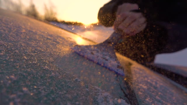 SLOW MOTION: Person scraping morning frost off a car window on winter morning