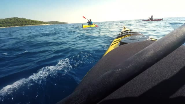 POV Person sea kayaking with friends in sunshine and stopping to relax Wide point of view shot of a person riding kayak along the sunny coastline with friends and stopping to take a breath. Shot in Croatia. recreational boat stock videos & royalty-free footage