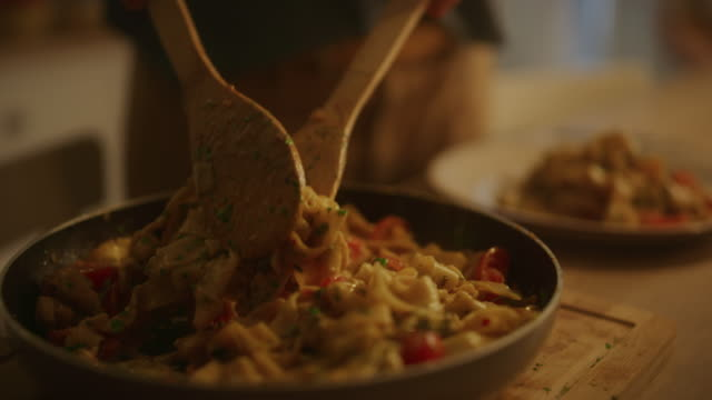 Person Serving Delicious Looking Pasta on the Plate. Serving Profesionally Cooked Pasta Dish in the Restaurant or for Romantic Dinner Meal at Home. Close-up Slow Motion Camera Shot