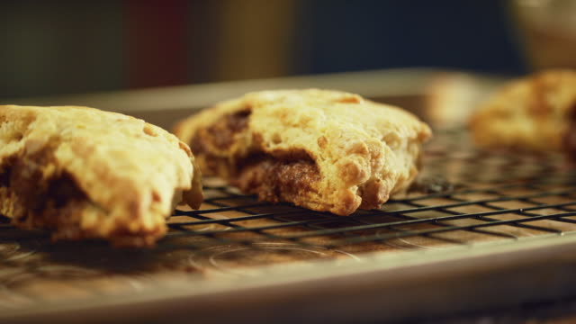 a person sets down a baking tray with homemade scones on to a countertop - scone filmów i materiałów b-roll