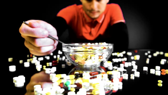 A person sitting in front of a bowl with pills is going to eat like a meal video