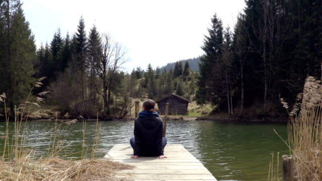 Person sitting on the piers on the lake in spring time. video