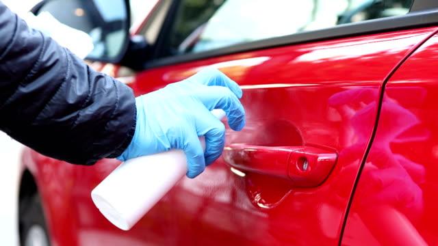 vídeos y material grabado en eventos de stock de persona pulverizando desinfectante y limpiando un coche con una toallita húmeda - manija