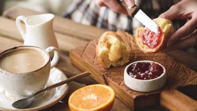 Person spread jam on sweet bun for breakfast