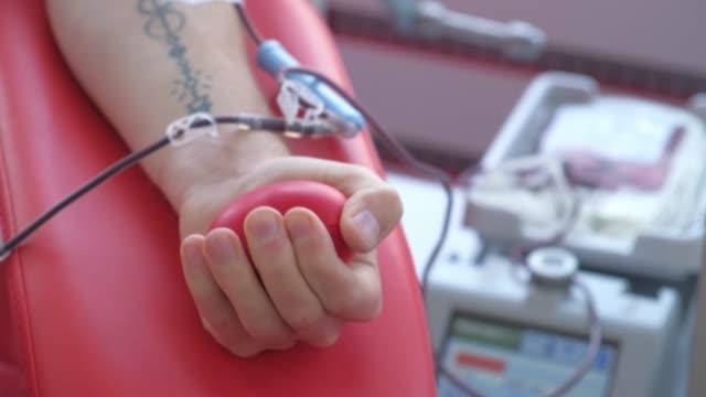 vídeos de stock e filmes b-roll de a person squeezes a ball while donating blood at a transfusion center. - blood donation