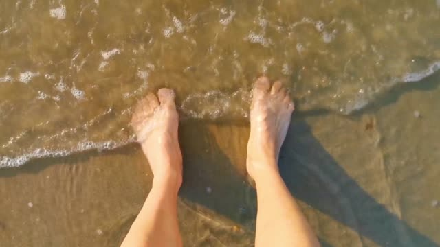 person standing with feet in the sand and water, sea waves coming by, relaxing in nature