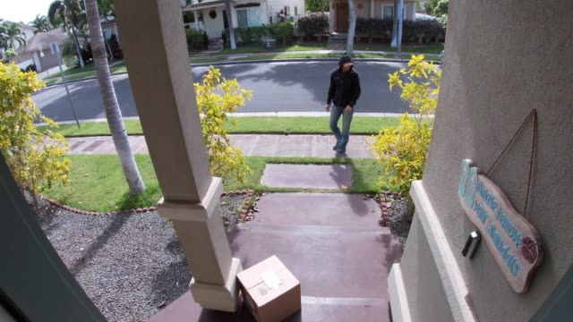 person stealing delivery package from porch steps, surveillance camera view - вор стоковые видео и кадры b-roll