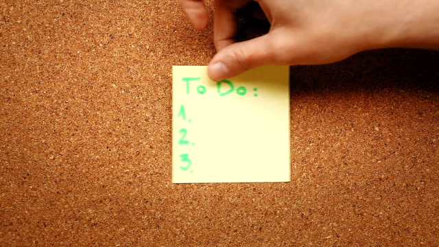 Person sticking a to do list on a cork board video