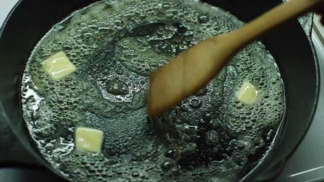 A Person Stirs Pats of Butter with a Wooden Spatula as They Melt in a Black Cast Iron Skillet on a Stove