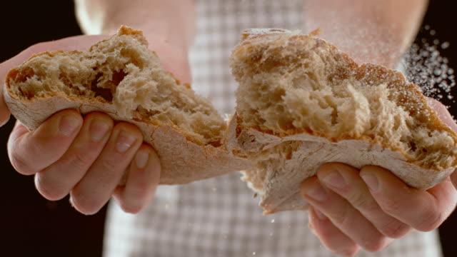 slo mo ld 사람이 집에서 구운 빵 한 덩어리를 찢어 - 식빵 한 덩어리 스톡 비디오 및 b-롤 화면