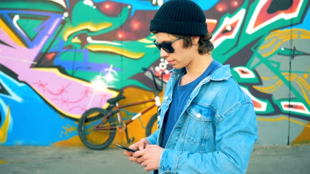 Person texting on his phone in a skatepark. Young stylish Caucasian male teenager.