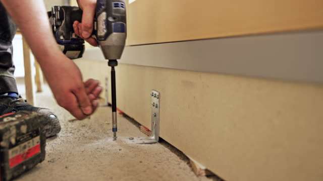 Person tightening screws into the floor with a machine