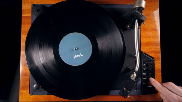 person turns on a musical player, placing a needle on a vinyl record. - giradischi video stock e b–roll