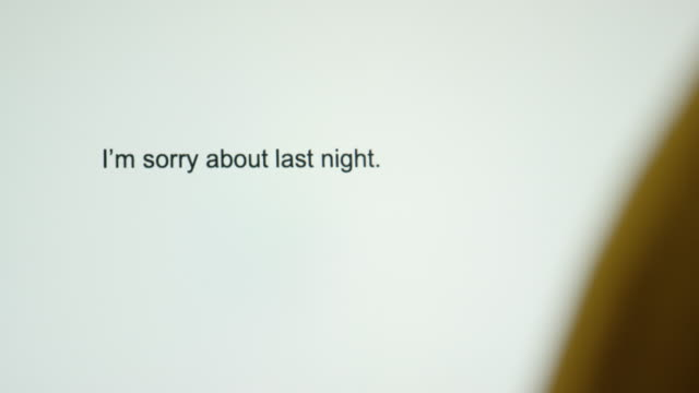 """a person types """"i'm sorry about last night"""" on their computer screen - chiedere scusa video stock e b–roll"""
