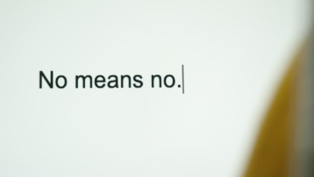 """a person types """"no means no"""" on their computer screen - proibizione video stock e b–roll"""