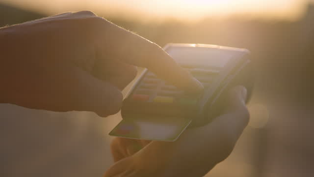 CLOSE UP: Person types their passcode on card reader keyboard on sunny evening