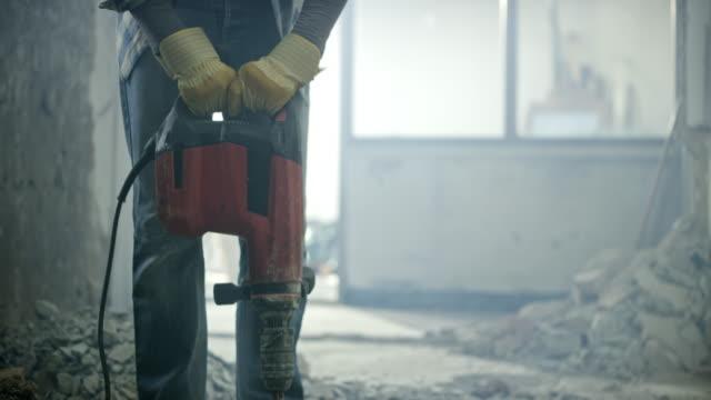 person som använder en jackhammer nagga betonggolvet - construction workwear floor bildbanksvideor och videomaterial från bakom kulisserna