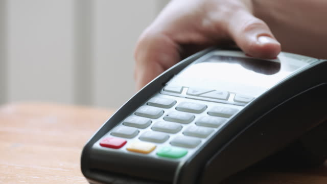 vídeos de stock e filmes b-roll de person using nfc technology on smart phone to pay - paying with card contactless