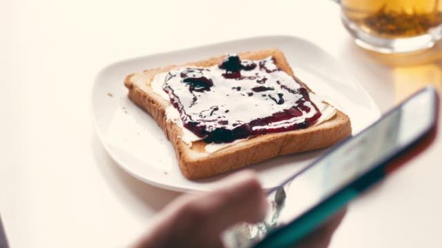 stockvideo's en b-roll-footage met persoon met behulp van de smartphone tijdens het eten toast met jam - geroosterd brood