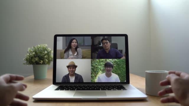 persona che utilizza la tecnologia di videoconferenza ai suoi amici asiatici con laptop in salotto durante la situazione del coronavirus. risoluzione 4k. - filippino video stock e b–roll