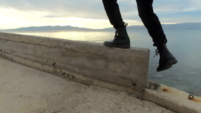 Person walking with boots along a walkway by the sea video