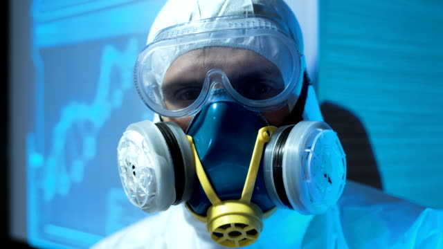 Person wearing a biohazard suit and mask video