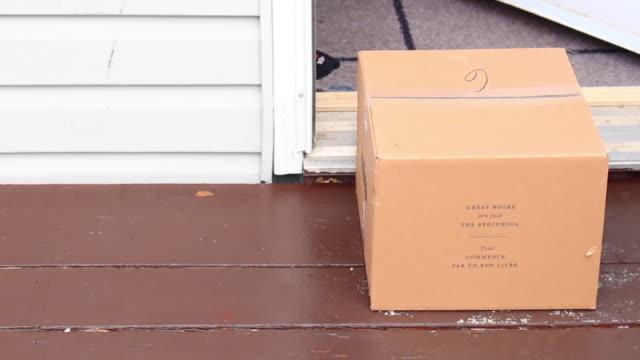 eldiven giyen bir kişi, bir ev girişinden bir teslim kutusu alıyor - sahanlık stok videoları ve detay görüntü çekimi
