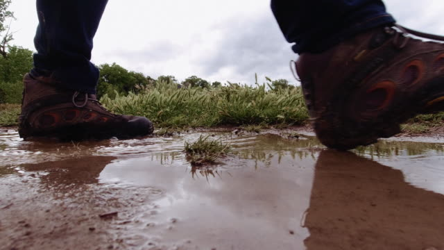 A Person with Hiking Boots and Jeans Walks through a Muddy Puddle of Water in an Uncultivated Area under a Stormy Sky A Person with Hiking Boots and Jeans Walks through a Muddy Puddle of Water in an Uncultivated Area under a Stormy Sky stepping stock videos & royalty-free footage