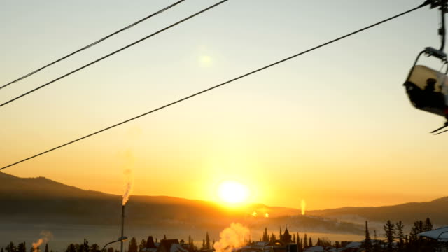 person with skies rides poma lift at popular winter resort