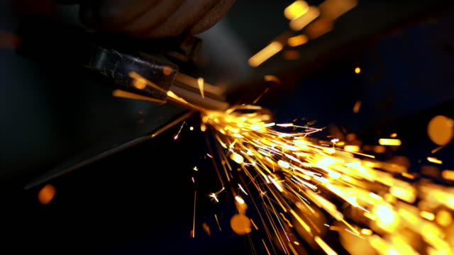slo mo person working with an angle grinder - rettificatrice video stock e b–roll