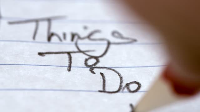 persona che scrive una lista di cose da fare. scatto macro - to do list video stock e b–roll