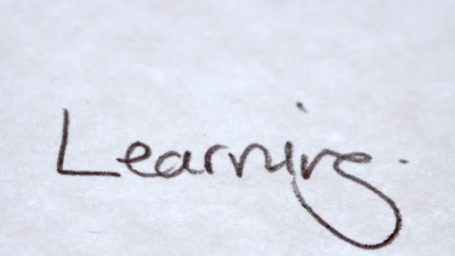 Une personne qui écrit le mot «Apprentissage» sur un morceau de papier - Vidéo
