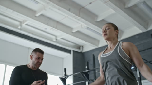personal coach yelling at woman while she skipping the rope - allenatore video stock e b–roll