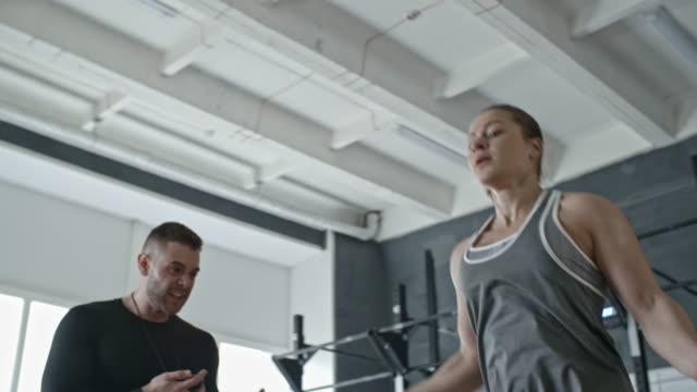 vídeos y material grabado en eventos de stock de entrenador personal gritándole a la mujer mientras ella saltando la cuerda - entrenador