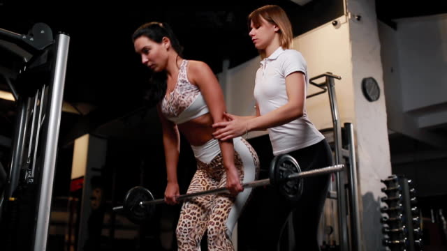 personal female trainer in white t-shirt helps to do the exercise deadlift female female client with long dark hair. exercising in a gym - personal trainer stock videos and b-roll footage