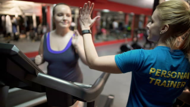 Personal fitness trainer motivating overweight girl during workout, high five video