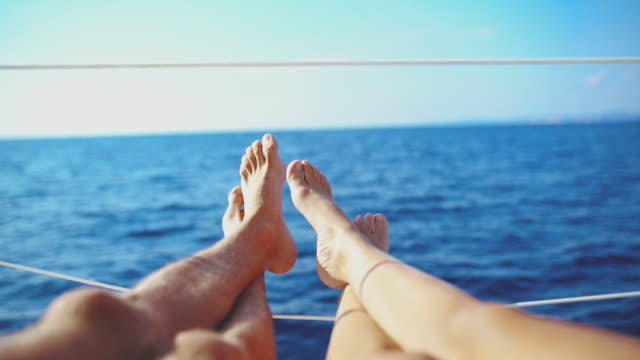 vídeos de stock e filmes b-roll de 4k personal perspective barefoot couple relaxing on sunny sailboat on sunny ocean, real time - veleiro