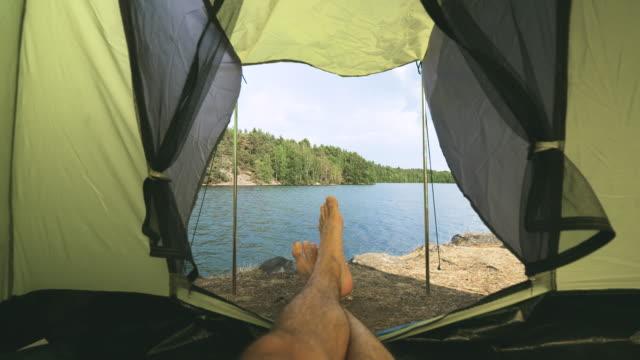 personligt perspektiv av en man i ett tält vid en sjö i sverige - pine forest sweden bildbanksvideor och videomaterial från bakom kulisserna