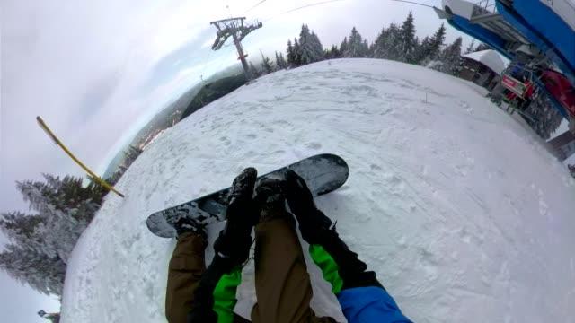 onun bağları bağlayan bir snowboard binici kişisel bakış açısı - mountain top stok videoları ve detay görüntü çekimi