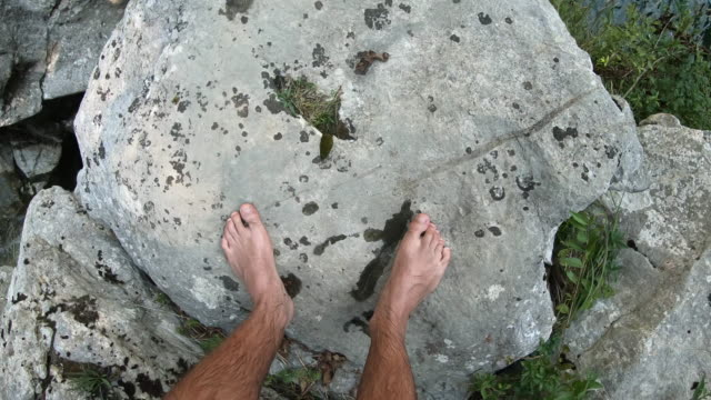 Personal Perspective of a Young Adult Man Standing on a Rock Above Stream Pool and Waterfall video