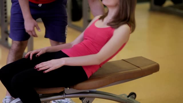 Personal trainer assisting woman in gym Personal trainer helps a girl to do exercises with dumbbells. Personal trainer assisting woman in gym. prop stock videos & royalty-free footage