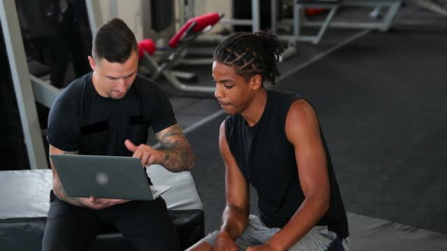 stockvideo's en b-roll-footage met personal trainer in overleg met een client - fitnessleraar