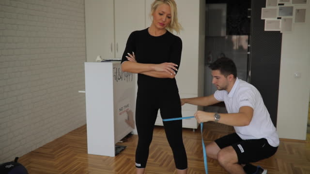 Personal trainer measuring woman in gym Personal trainer  measuring  woman's circumference of leg to see results after workout measuring stock videos & royalty-free footage