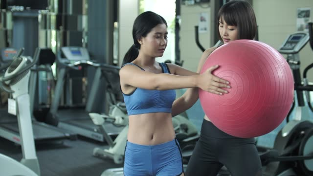 Personal trainer teaching client how to exercising with Yoga Ball video