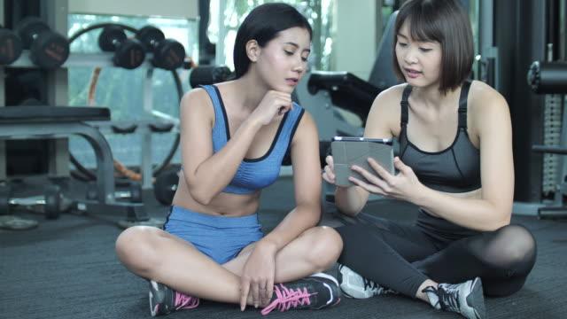 personlig utbildning på tablet pc - gym skratt bildbanksvideor och videomaterial från bakom kulisserna