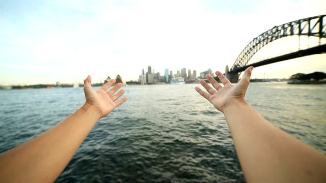 Person's arms stretch towards Sydney skyline, Australia video