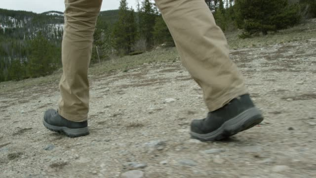 A Person's Feet in Hiking Boots Hike in the Rocky Mountains of Colorado under an Overcast Sky in Winter